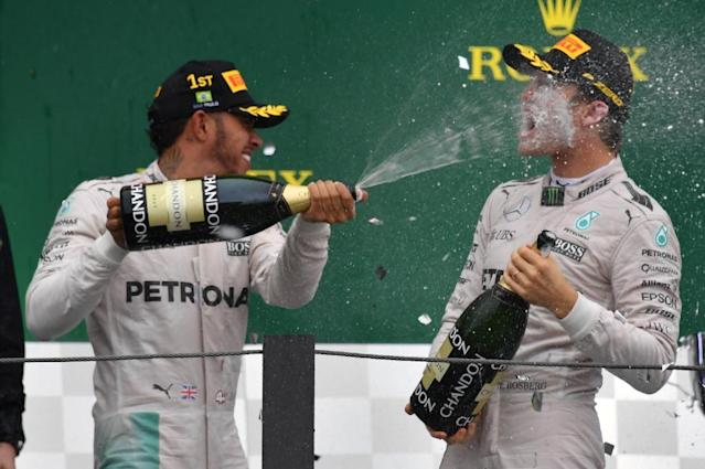 Mercedes driver Lewis Hamilton (L) celebrates after winning the Brazilian Grand Prix ahead of title rival and Mercedes teammate Nico Rosberg (R) on November 13, 2016 (AFP Photo/Nelson Almeida)