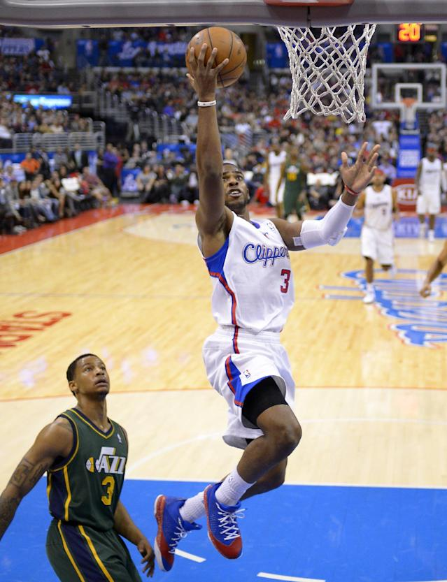 Los Angeles Clippers guard Chris Paul, right, puts up a shot as Utah Jazz guard Trey Burke defends during the first half of an NBA basketball game, Saturday, Dec. 28, 2013, in Los Angeles. (AP Photo/Mark J. Terrill)