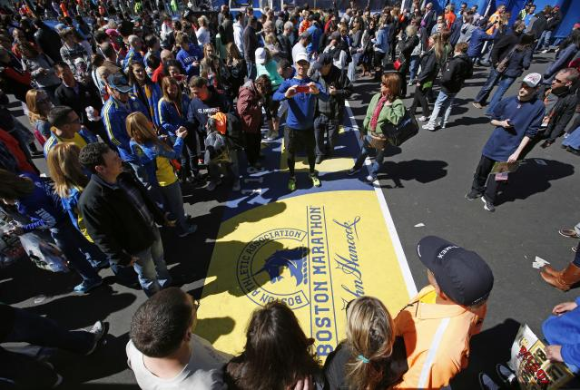 A large crowd gathers to pose for photos at the Boston Marathon finish line, one day before the race, Sunday, April 20, 2014, in Boston. (AP Photo/Robert F. Bukaty)