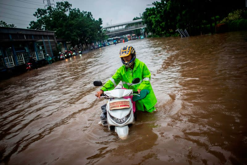 A man walks with his scooter through flood water after heavy rain in Jakarta