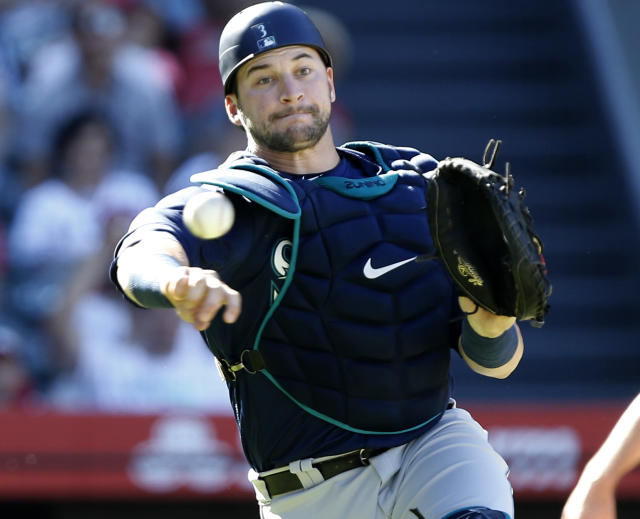 Seattle Mariners catcher Mike Zunino throws to first after Los Angeles Angels designated hitter Shohei Ohtani struck out swinging but got on base after a wild pitch during the eighth inning of a baseball game in Anaheim, Calif., Sunday, Sept. 16, 2018. (AP Photo/Alex Gallardo)
