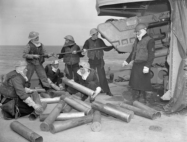 <p>Title: A 4.7-inch (12 cm) gun crew of the destroyer HMCS Algonquin piling shell cases and sponging out the gun after bombarding German shore defences in the Normandy beachhead.<br /> Photographer: Arless, Richard Graham, 1919-<br /> Location: Normandy, France:<br /> Description: (Front, L-R): Ordinary Seamen K. Allen and R. De Guire. (Rear, L-R): Able Seamen G. Trevisanutto and J. Van Dyke, Ordinary Seamen A. Irwin and E. Mathetuk.<br /> Date: June 1944.<br /> Credit: Library Archives Canada </p>