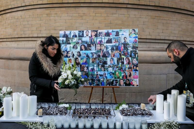 Mourners attend a memorial for the victims of a Ukrainian passenger plane which was shot down in Iran
