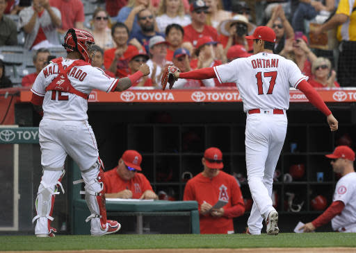 Los Angeles Angels catcher Martin Maldonado, left, and starting pitcher Shohei Ohtani, of Japan, congratulate each other after the top of the fifth inning of a baseball game against the Tampa Bay Rays, Sunday, May 20, 2018, in Anaheim, Calif. (AP Photo/Mark J. Terrill)