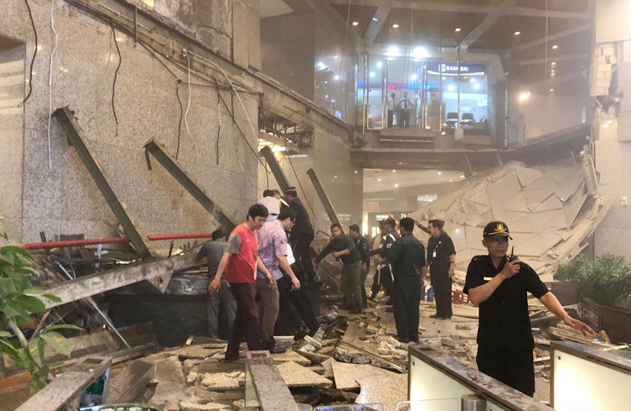 <p>Indonesian security stand near the ruin of a structure inside the Jakarta Stock Exchange tower in Jakarta, Indonesia, Jan. 15, 2018. A structure inside the Jakarta Stock Exchange tower collapsed Monday, injuring at least several people and forcing a chaotic evacuation. (Photo: AP) </p>