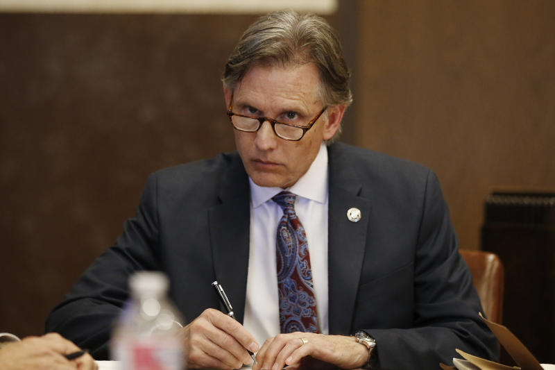 Oklahoma Attorney General Mike Hunter takes notes during a recess in a hearing to settle disagreements between Johnson & Johnson and the State over Judge Thad Balkman's final judgement in the opioid lawsuit, Tuesday, Oct. 15, 2019 in Norman, Okla. (AP Photo/Sue Ogrocki)