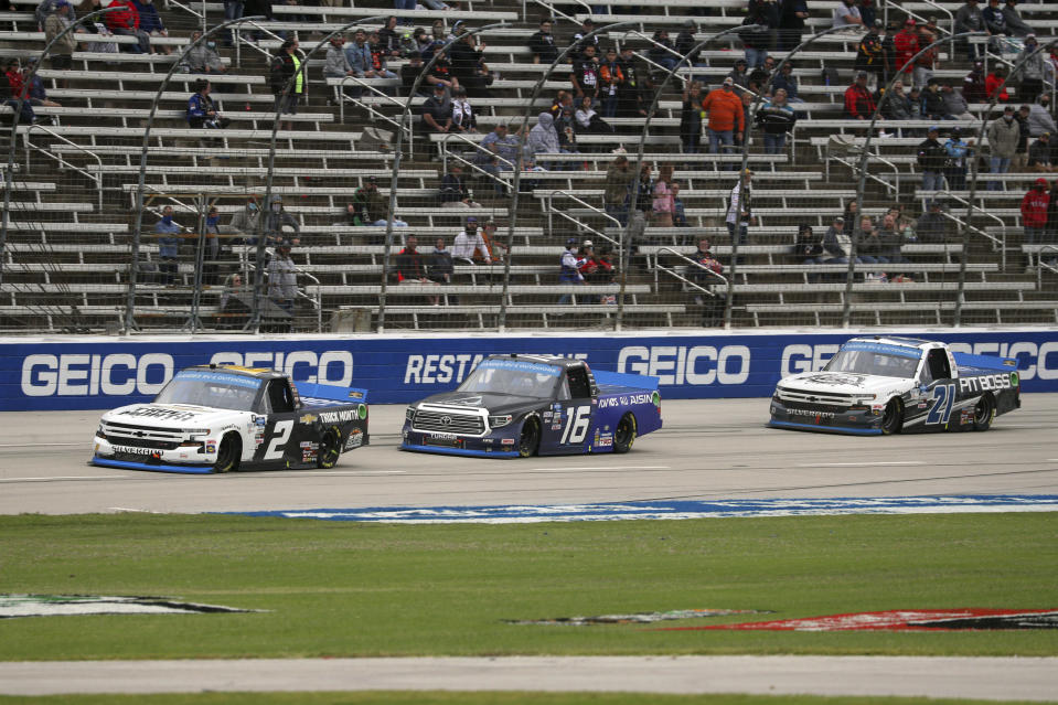 NASCAR Texas Trucks Series driver Sheldon Creed (2) tries to hold off Austin Hill (16) and Zane Smith (21) while going into the final lap during an auto race at Texas Motor Speedway in Fort Worth, Texas, Sunday, Oct. 25, 2020. (AP Photo/Richard W. Rodriguez)