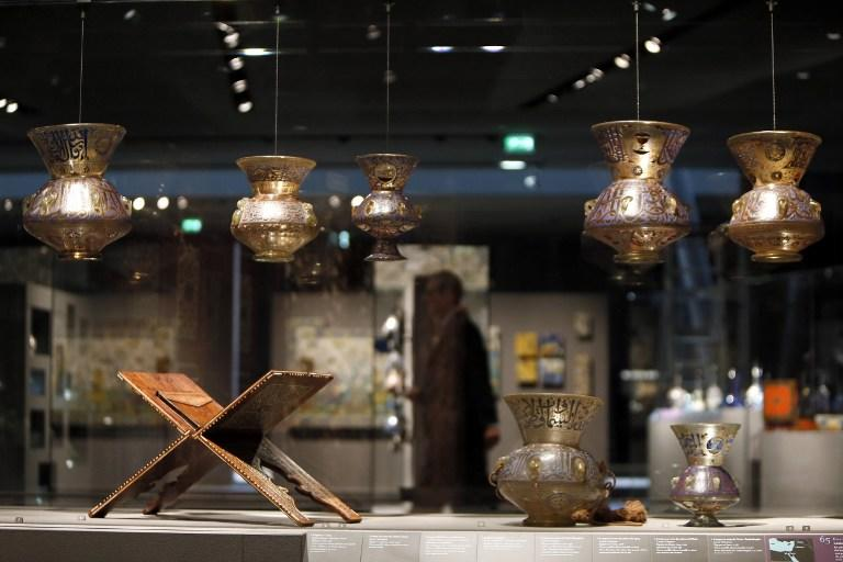 """A lectern for Koran (L) and Lamps from Egypt or Syria dating from the 14th century are displayed on September 17, 2012 in Paris, at the new Department of Islamic Arts at the Louvre, the largest of its kind in Europe, with 3,000 artefacts on display, gathered from Spain to India and dating back to the seventh century AD. Intended to celebrate """"The Radiant Face of a Great Civilization"""" the 100-million-euro project - largely financed by donors from across the Islamic world - will be inaugurated by French President ahead of its official opening on September 18. AFP PHOTO / KENZO TRIBOUILLARD"""