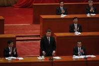 Party officials applaud as Chinese President Xi Jinping, standing, delivers his speech at the commemorating conference on the 70th anniversary of the Chinese army entering North Korea to resist the U.S. army, at the Great Hall fo the People in Beijing, Friday, Oct. 23, 2020. (AP Photo/Andy Wong)