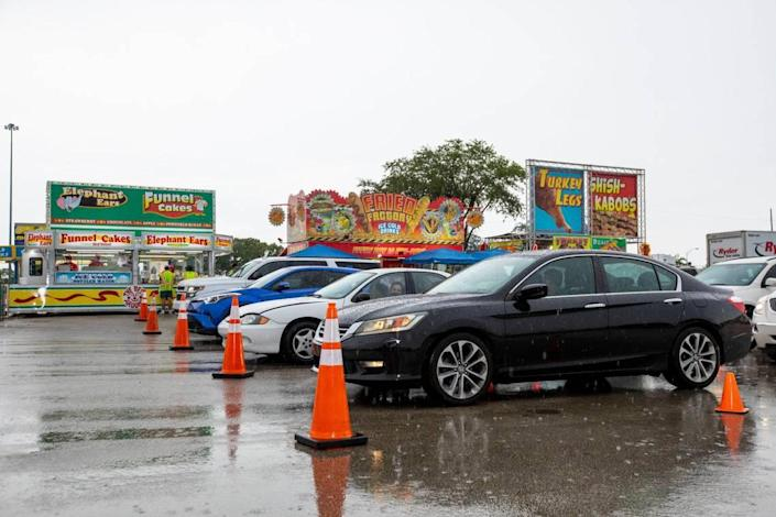 Food runners deliver orders to drivers as they wait in their cars in line during the Miami-Dade County Youth Fair food drive-through in Miami, Florida on Saturday, July 11, 2020.