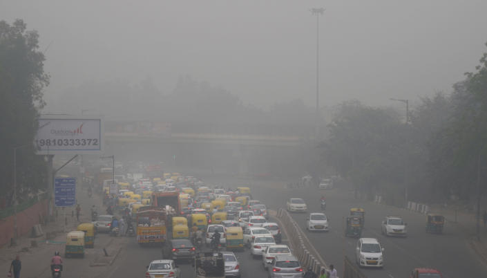 """In this Sunday, Nov. 3, 2019, file photo, vehicles wait for a signal at a crossing as the city enveloped in smog in New Delhi, India. Authorities in New Delhi are restricting the use of private vehicles on the roads under an """"odd-even"""" scheme based on license plates to control vehicular pollution as the national capital continues to gasp under toxic smog. (AP Photo/Manish Swarup, File)"""