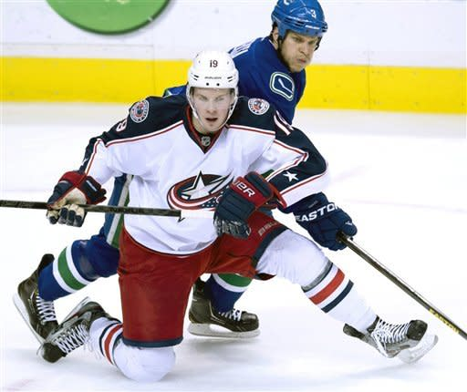 Columbus Blue Jackets' Ryan Johansen (19) fights for control of the puck with Vancouver Canucks' Kevin Bieksa (3) during the second period of an NHL hockey game in Vancouver, British Columbia, Tuesday, March 26, 2013. (AP Photo/The Canadian Press, Jonathan Hayward)