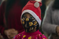 An Indian Christian girl wearing a Santa cap and a face mask as a precaution against the coronavirus attends the Christmas mass at a church in Gauhati, India, Friday, Dec. 25, 2020. (AP Photo/Anupam Nath)