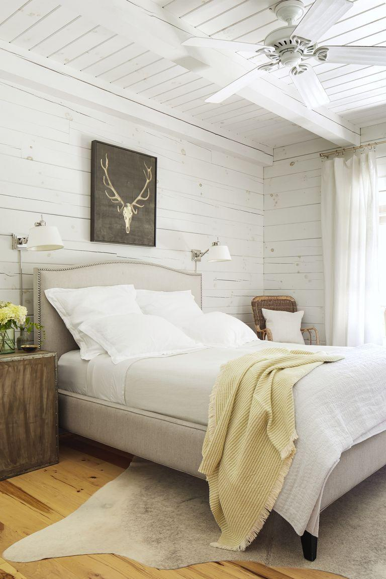 <p>All-white shiplap walls and petite sconces bring charm to this light-filled bedroom. </p>