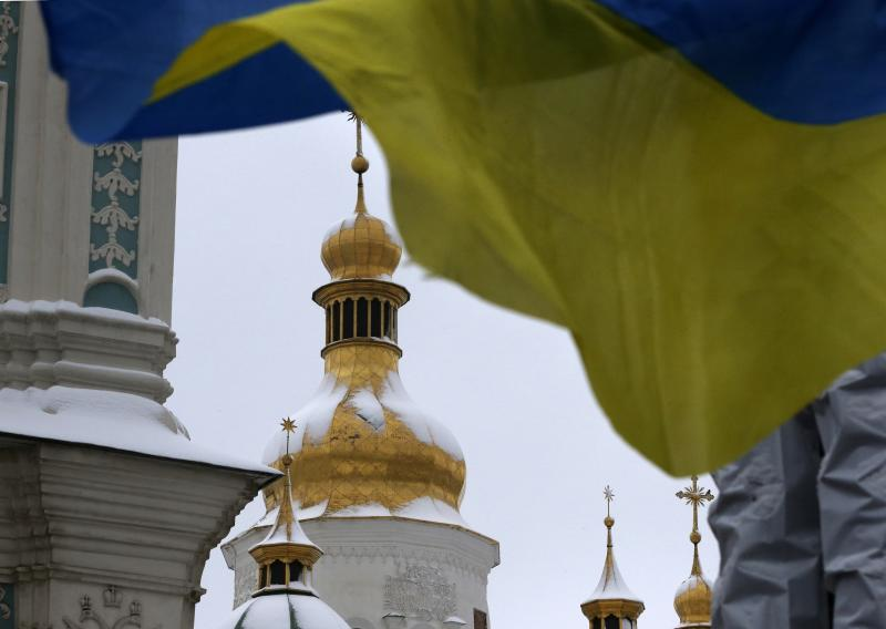 A Ukrainian national flag flutters in the wind as people gather to support independent Ukrainian church near the St. Sophia Cathedral in Kiev, Ukraine, Saturday, Dec. 15, 2018. Ukraine's Orthodox clerics gather for a meeting Saturday that is expected to form a new, independent Ukrainian church, and Ukrainian authorities have ramped up pressure on priests to support the move. (AP Photo/Efrem Lukatsky)