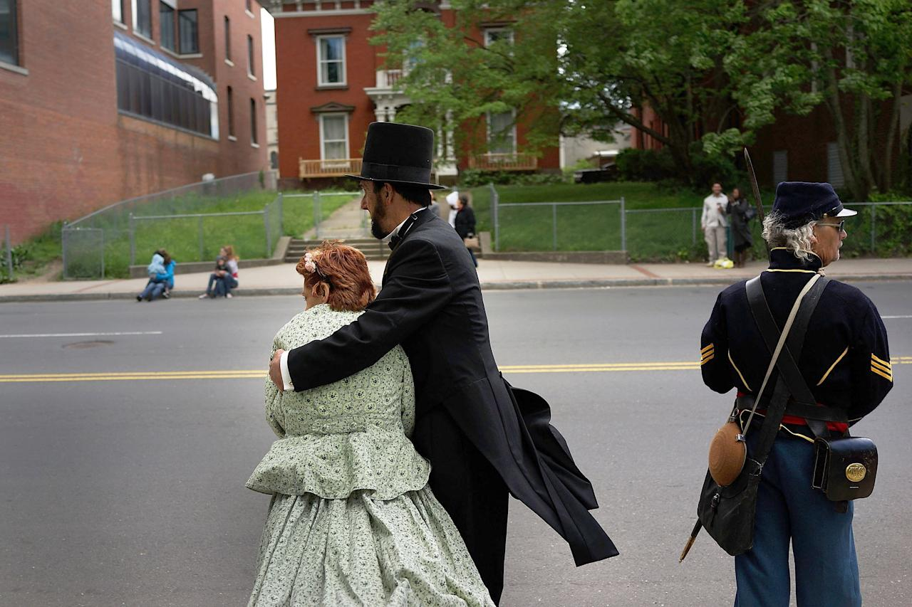 WATERBURY, CT - MAY 26: A couple dressed as Abraham Lincoln and Mary Lincoln embrace as they wait for the Memorial Day Parade to pass on May 26, 2013 in Waterbury, Connecticut. Memorial Day is a federal holiday in America and has been celebrated since the end of the Civil War. Waterbury, once a thriving industrial city with one of the largest brass manufacturing bases in the world, has suffered economically in recent decades as manufacturing jobs have left the area. (Photo by Spencer Platt/Getty Images)
