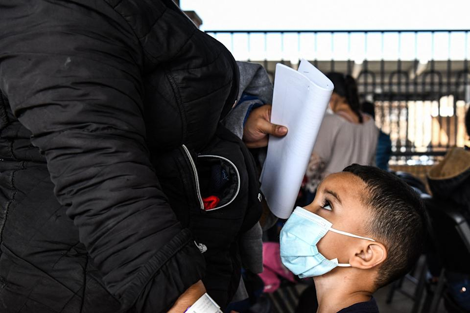 A migrant boy from Central America waits with her mother for a bus after they are dropped off by the U.S. Customs and Border Protection at a bus station near the Gateway International Bridge, between the cities of Brownsville, Texas, and Matamoros, Mexico, on March 15 in Brownsville, Texas. (Photo: CHANDAN KHANNA via Getty Images)