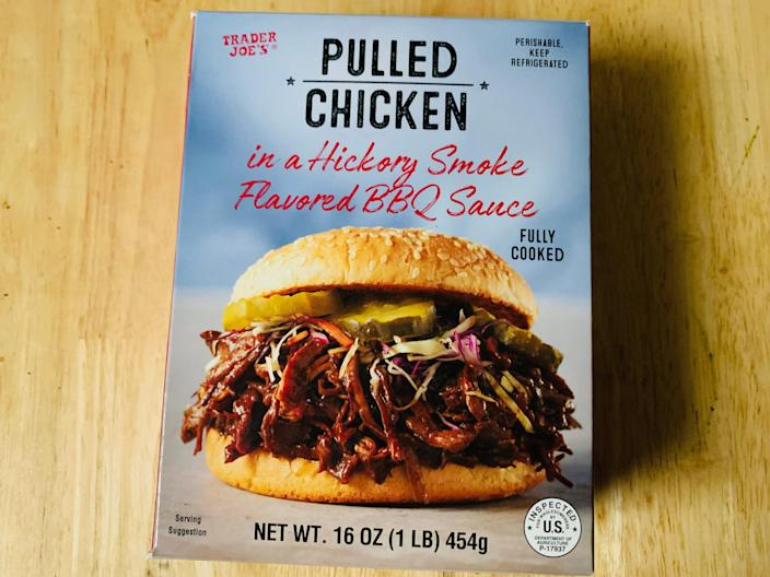 trader joe's barbecue pulled chicken in it's original blue box on a light wood table