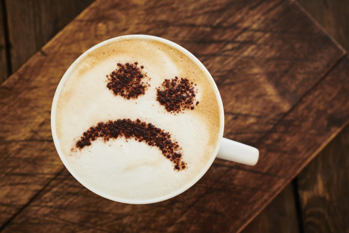 Cappuccino Coffee topped with a chocolate unhappy smiley face.