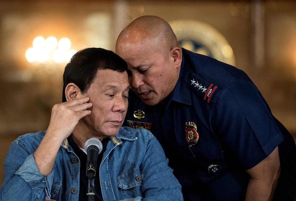 File Rodrigo Duterte (L) talking to then Philippine National Police (PNP) director general Ronald Dela Rosa (R) during a press conference at the Malacanang palace in Manila. (POOL/AFP via Getty Images)