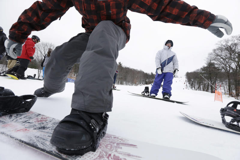 Snowboarders traverse a slope as they make their way toward a chairlift at Blue Hills Ski Area Sunday, Dec. 15, 2013 in Canton, Mass. The National Weather Service says parts of Massachusetts, Connecticut and Rhode Island will see snow accumulation of between 6 inches and a foot. (AP Photo/Steven Senne)