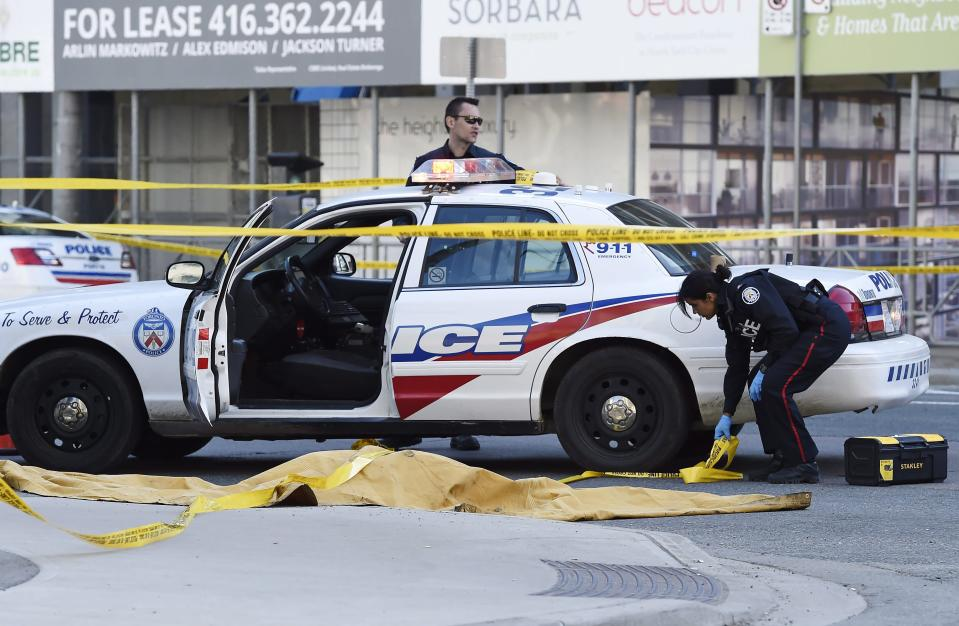 <p>Police officers secure an area around a covered body in Toronto after a van mounted a sidewalk crashing into a number of pedestrians on Monday, April 23, 2018. THE CANADIAN PRESS/Nathan Denette </p>