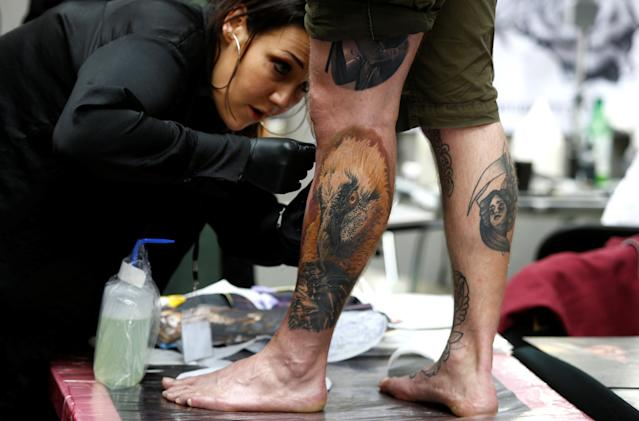 <p>A tattoo artist prepares a design on the leg of a man at the London Tattoo Convention, in London, Britain, Sept. 23, 2017. (Photo: Peter Nicholls/Reuters) </p>