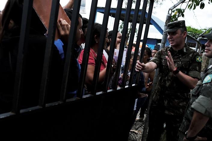 <p>A military officer (R) talks to Venezuelans as they queue to show their passports or identity cards at the Pacaraima border control, Roraima state, Brazil, Aug. 8, 2018. (Photo: Nacho Doce/Reuters) </p>