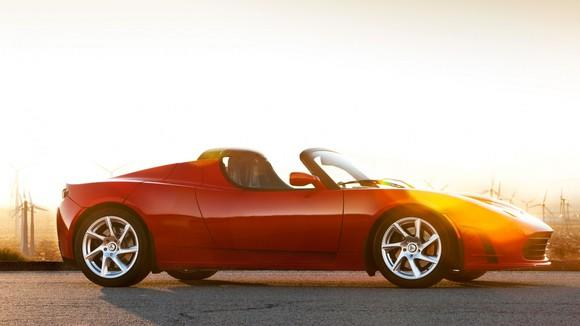 Red Tesla roadster on a road in front of a bright sunny background.