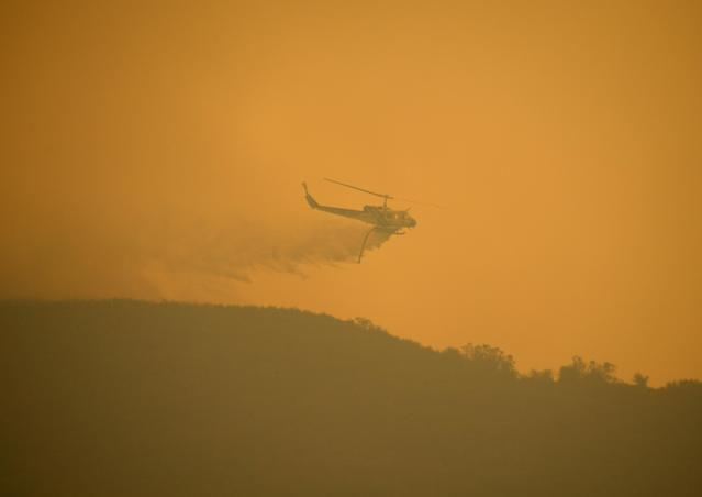 NEWBURY PARK, CA - MAY 03: A Kern County Fire Department helicopter drops water over a hillside as a wildfire in Pt. Mugu State Park charges back towards homes on May 3, 2013 in Newbury Park, California. Hundreds of firefighters continue to battle wind and dry conditions with over 10,000 acres burned. (Photo by Kevork Djansezian/Getty Images)