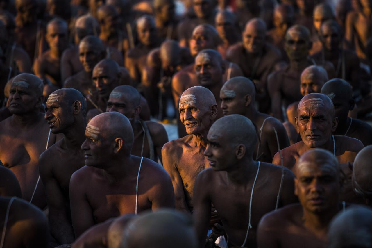 ALLAHABAD, INDIA - FEBRUARY 08: Naga sadhus, naked Hindu holy men, sit during an initiation ceremony on the banks of the Ganges river during the Maha Kumbh Mela on February 8, 2013 in Allahabad, India. The Maha Kumbh Mela, believed to be the largest religious gathering on earth, is held every 12 years on the banks of Sangam, the confluence of the holy rivers Ganga, Yamuna and the mythical Saraswati. The Kumbh Mela alternates between the cities of Nasik, Allahabad, Ujjain and Haridwar every three years. The Maha Kumbh Mela celebrated at Sangam, is the largest and holiest, celebrated over 55 days, and is expected to attract over 100 million pilgrims who will bathe in holy waters to wash away their sins. (Photo by Daniel Berehulak/Getty Images)