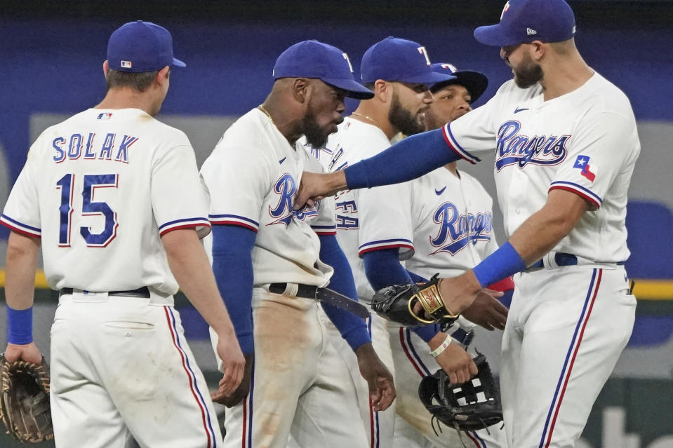 Texas Rangers center fielder Adolis Garcia, second from left, absorbs a playful punch from teammate Joey Gallo, right, as they celebrate their win over the Seattle Mariners after a baseball game Saturday, May 8, 2021, in Arlington, Texas. (AP Photo/Louis DeLuca)