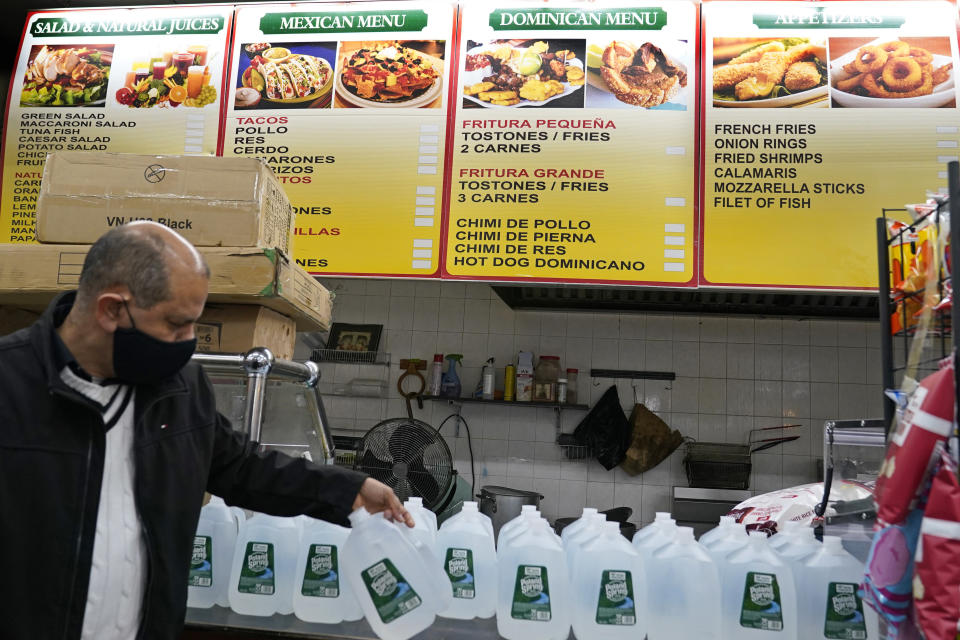 Bodega owner Francisco Marte restocks his currently unused food service counter with water bottles, Wednesday, Feb. 10, 2021, in the Bronx borough of New York. Marte president of the Bodega and Small Business Group, which represents bodegas in New York, said he's been lobbying local officials to set aside COVID-19 vaccine appointments for bodega workers, many of whom are unaware they are eligible. He hopes that the recent opening of a large vaccination site at Yankee stadium will make access easier. (AP Photo/Kathy Willens)