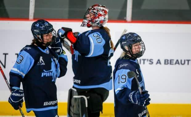 Team Bauer's Rebecca Leslie, right, celebrates with teammates Alexandra Labelle, left, and goalie Ann-Renee Desbiens during a Monday victory. The team picked up another win Tuesday after beating Team Scotiabank 6-1 at the Dream Gap Tour in Calgary. (Jeff McIntosh/The Canadian Press - image credit)