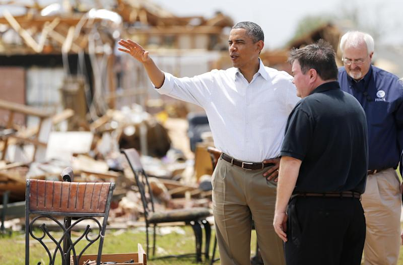 FILE - In a Sunday, May 26, 2013 file photo, President Barack Obama tours the Plaza Towers addition in Moore, Okla., beside Moore Mayor Glenn Lewis. In his 20 years as mayor of the Oklahoma City suburb, Lewis has already rebuilt his town twice, grappling with the aftermath of tornadoes so enormous the probability they strike is barely 2 percent. Yet Moore has been slammed by EF5 tornadoes, the largest on the rating scale, twice. (AP Photo/The Oklahoman, Bryan Terry, Pool, File)