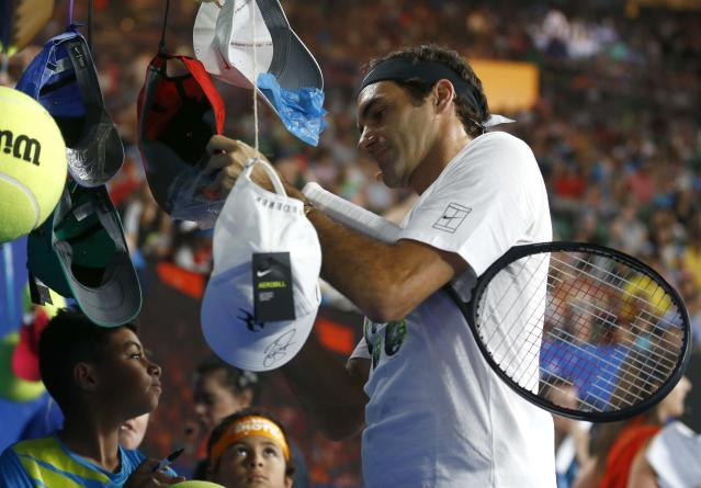 Tennis - Australian Open - Kids Tennis Day - Rod Laver Arena, Melbourne, Australia, January 13, 2018. Roger Federer of Switzerland signs autographs during Kids Tennis Day before the Australian Open tennis tournament. REUTERS/Thomas Peter