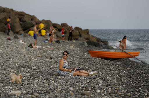 FILE - In this Friday, June 22, 2018 filer, a woman plays fetch with her dog on the Black Sea waterfront during the 2018 soccer World Cup in Sochi, Russia. Sochi in the summer is a whole lot different than what fans saw during the Winter Olympics. The snow is replaced by lots of sun as Russia's summertime playground explodes in a scene more akin to Southern California or Miami Beach than Siberia. World Cup fans have been taking advantage of the beaches, waterparks and other warm-weather activities, and teams have been eager to train there. (AP Photo/Rebecca Blackwell, File)