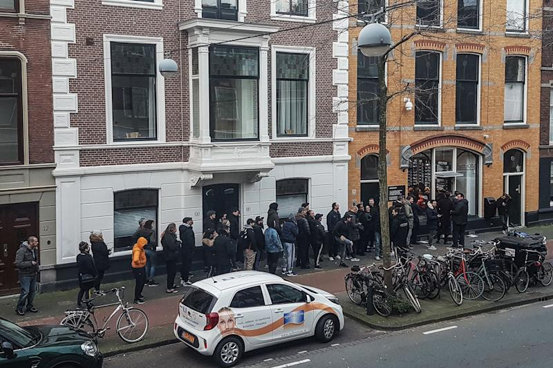"People queue outside a cannabis coffee shop on March 15, 2020, in The Hague, after the Dutch government ordered the closing of all schools, bars, restaurants, sex clubs and cannabis cafes in a bid to fight the spread of COVID-19, the new coronavirus. - Queues quickly built up at ""coffee shops"" where cannabis is sold after the announcement, which follows pressure on the government to follow the lead of other European countries. (Photo by Sara MAGNIETTE / AFP) (Photo by SARA MAGNIETTE/AFP via Getty Images)"