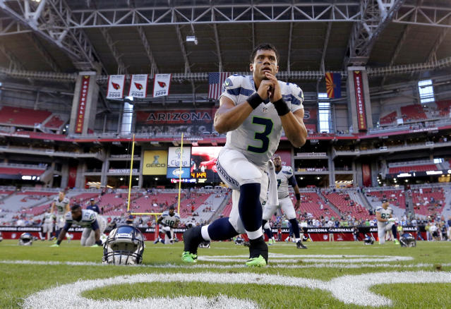 Seattle Seahawks quarterback Russell Wilson stretches as the Seahawks prepared for an NFL football game against the Arizona Cardinals, Thursday, Oct. 17, 2013, in Glendale, Ariz. (AP Photo/Ross D. Franklin)