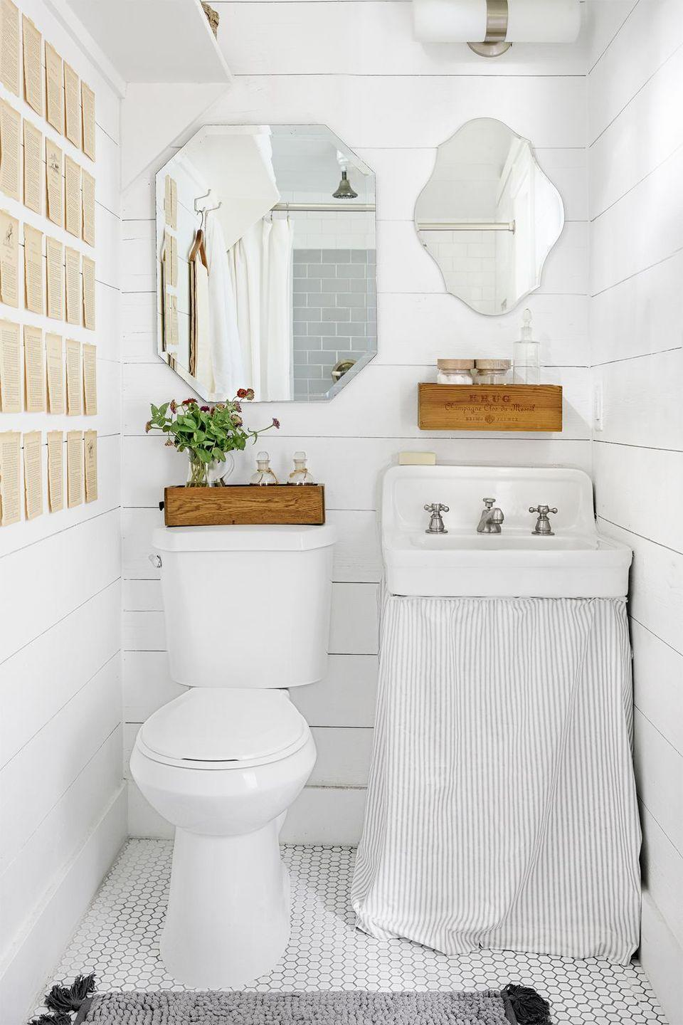 """<p>Paige simply attached a piece of striped fabric to her bathroom sink—instead of installing a bulky set of drawers—to cover up her necessities. The double mirrors also create the illusion of more space.</p><p><a class=""""link rapid-noclick-resp"""" href=""""https://www.amazon.com/Tiny-House-Living-Building-Square/dp/1440333165/?tag=syn-yahoo-20&ascsubtag=%5Bartid%7C10050.g.1887%5Bsrc%7Cyahoo-us"""" rel=""""nofollow noopener"""" target=""""_blank"""" data-ylk=""""slk:SHOP TINY HOUSE BOOKS"""">SHOP TINY HOUSE BOOKS</a></p>"""