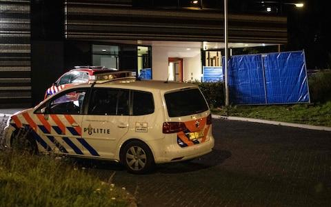 A police car is parked at a fire station in Amsterdam, where a car hit the facade after a shooting - Credit: AFP