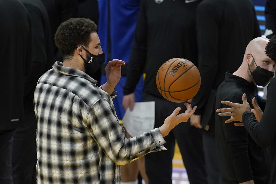 Injured Golden State Warriors guard Klay Thompson spins a ball during a timeout in the second half of the team's NBA basketball game against the Brooklyn Nets in San Francisco, Saturday, Feb. 13, 2021. (AP Photo/Jeff Chiu)