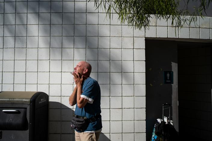 Terrance Whitten, 67, dries his face after washing in the public restroom at the Pan Pacific Park on Friday.