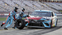 Crew members perform a pit stop on Kyle Busch's car during qualifying for Saturday's NASCAR All-Star auto race at Charlotte Motor Speedway in Concord, N.C., Friday, May 17, 2019. (AP Photo/Chuck Burton)