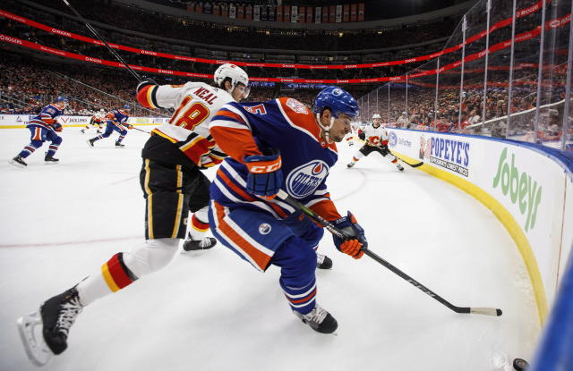 Calgary Flames' James Neal (18) and Edmonton Oilers' Kevin Gravel (5) battle for the puck during first period NHL hockey action in Edmonton, Alberta on Sunday, Dec. 9, 2018. (Jason Franson/The Canadian Press via AP)
