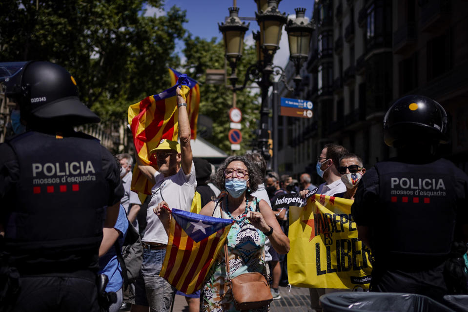 """Demonstrators hold """"esteladas"""" or Catalan pro-independence flags during a protest against Spain's prime minister Pedro Sanchez outside the Gran Teatre del Liceu in Barcelona, Spain, Monday, June 21, 2021. Sanchez's said Monday that the Spanish Cabinet will approve pardons for nine separatist Catalan politicians and activists imprisoned for their roles in the 2017 push to break away from Spain. (AP Photo/Joan Mateu)"""
