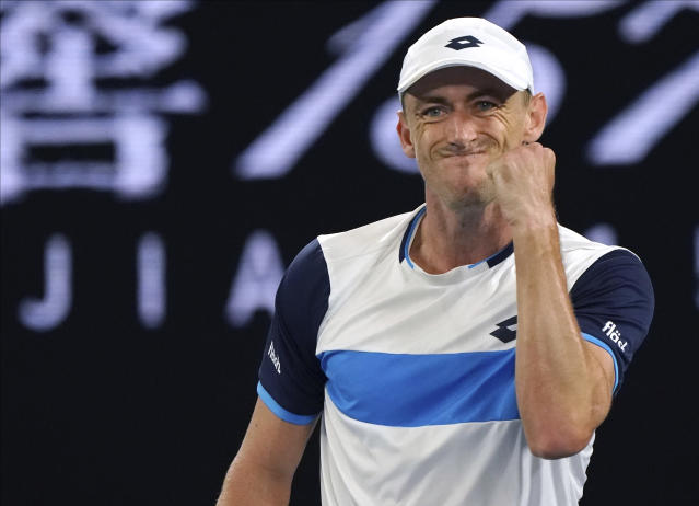 Australia's John Millman celebrates a point win over Switzerland's Roger Federer during their third round match at the Australian Open tennis championship in Melbourne, Australia, Friday, Jan. 24, 2020. (AP Photo/Lee Jin-man)