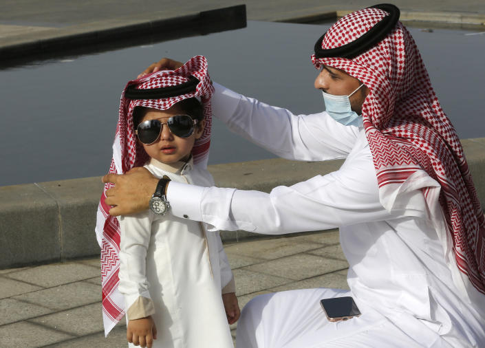 """A Saudi man arranges his son's traditional """"Ghutra"""", or head cover, after performing Eid al-Fitr prayer marking the end of the holy fasting month of Ramadan in Jiddah, Saudi Arabia, Thursday, May 13, 2021. (AP Photo/Amr Nabil)"""