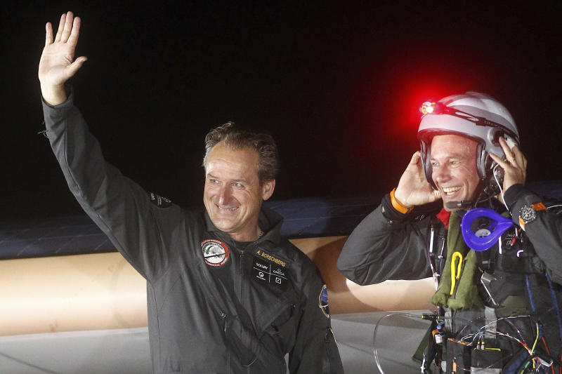 Solar Impulse pilots Bertrand Piccard, right, and Andre Borschberg, left, are all smiles upon arrival at Rabat airport, Morocco, Tuesday, June 5, 2012. The experimental solar-powered airplane landed in Morocco's capital late Tuesday after a 20-hour trip from Madrid in the first transcontinental flight by a craft of its type. The mission is being described as a final dress rehearsal for a round-the-world flight with a new and improved plane in 2014. (AP Photo/Abdeljalil Bounhar)