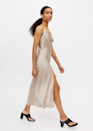 """The Champagne color of this slinky slip dress is perfection. Have a <a href=""""https://www.glamour.com/gallery/beach-wedding-guest-dresses?mbid=synd_yahoo_rss"""" rel=""""nofollow noopener"""" target=""""_blank"""" data-ylk=""""slk:beach wedding"""" class=""""link rapid-noclick-resp"""">beach wedding</a> on your cal? This would be a strong contender. $59, Urban Outfitters. <a href=""""https://www.urbanoutfitters.com/shop/dress-forum-side-button-midi-slip-dress"""" rel=""""nofollow noopener"""" target=""""_blank"""" data-ylk=""""slk:Get it now!"""" class=""""link rapid-noclick-resp"""">Get it now!</a>"""